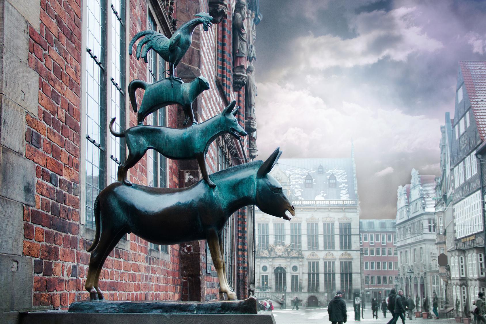 Bronzefigur der Bremer Stadtmusikanten vor dem Bremer Rathaus mit Aussicht auf den Rathausplatz.