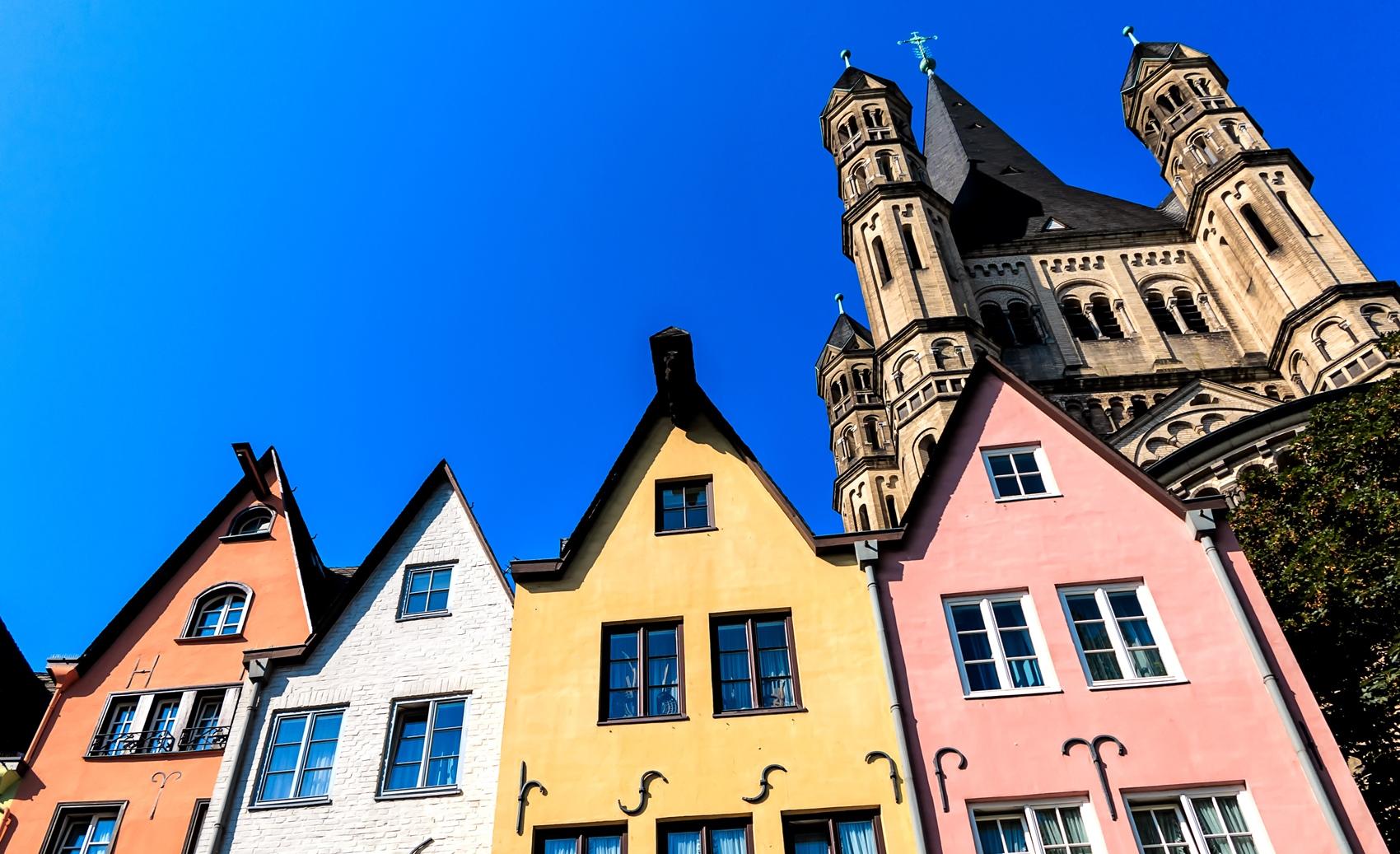 Eine Reihe bunter Huser am Rheinufer vor Gro St. Martin Kirche in Kln
