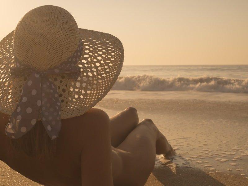 Frau sonnt sich nackt am Strand