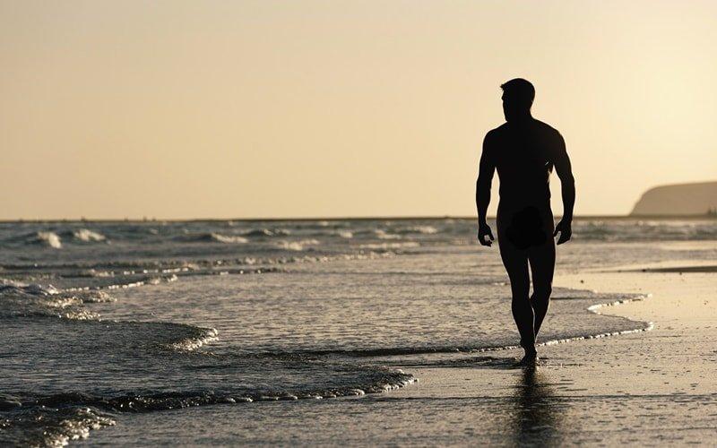 Mann läuft nackt am Strand