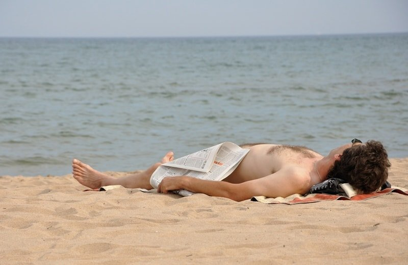 Mann sonnt sich am Strand