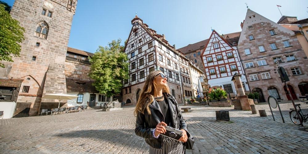 Junge Frau mit Kamera vor Altbauten in Nürnberg