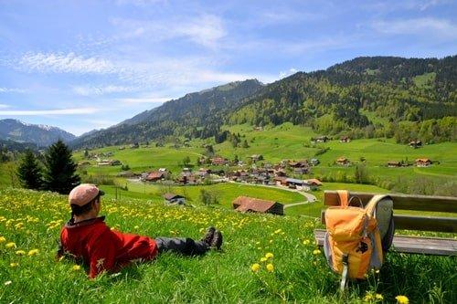 Wanderer erholt sich auf einer Wiese mit Blick auf die Berge
